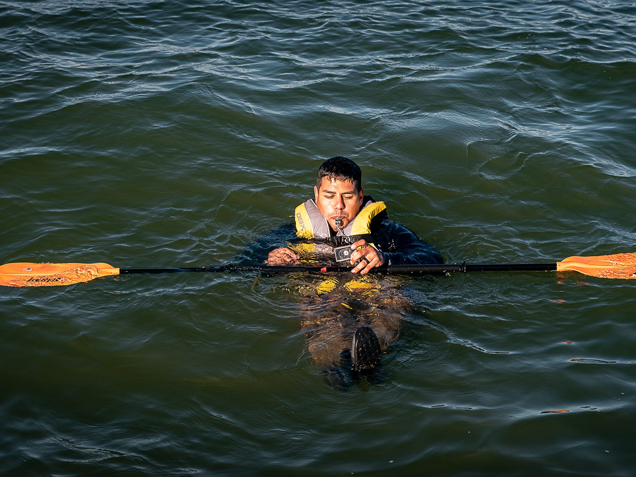 Petty Officer 1st Class Jose Termini uses a whistle and signal mirror as proper cold-water survival techniques during a Tuesday, Oct. 30, 2018 U.S. Coast Guard demonstration in Cape Charles, Virginia.