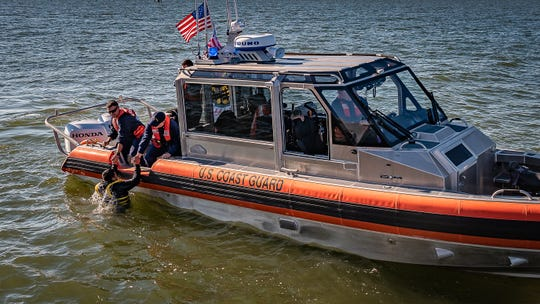 A U.S. Coast Guard member is pulled aboard a boat after being in the water demonstrating survival techniques on Tuesday, Oct. 30, 2018 in Cape Charles, Virginia.