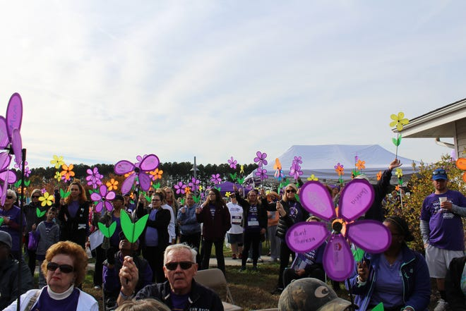 People hold their flowers prior to start of the 2017 Walk to End Alzheimer's in Salisbury.