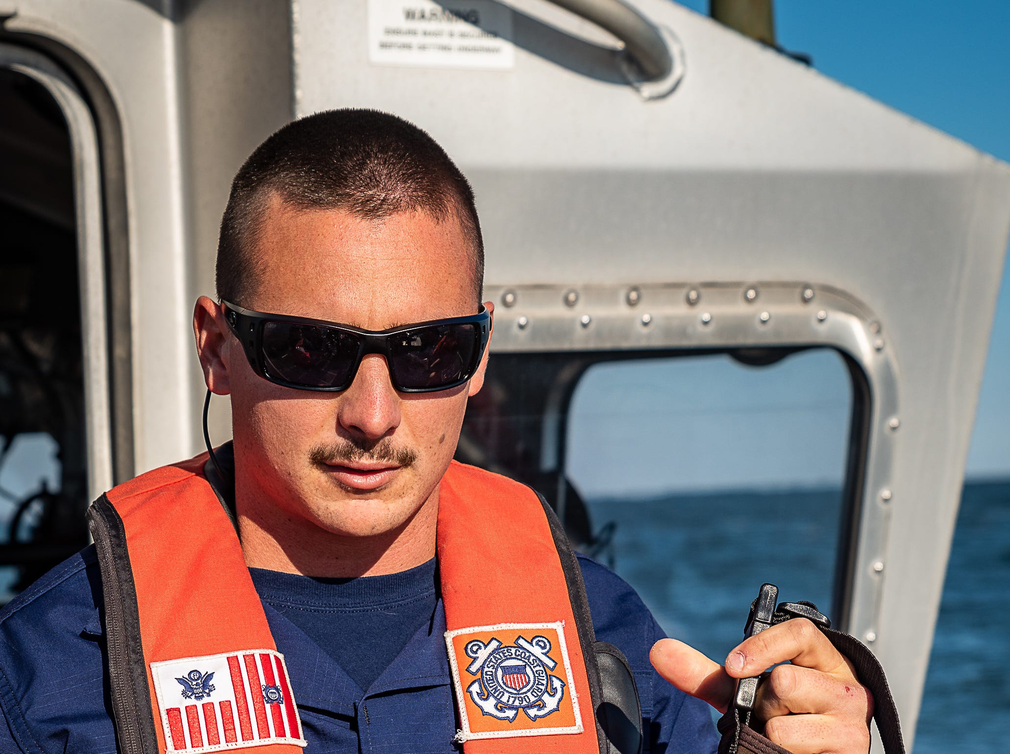 Boatswain Mate 2nd Class Blake Westforth talks about survival techniques during a U.S. Coast Guard demonstration on Oct. 30, 2018.