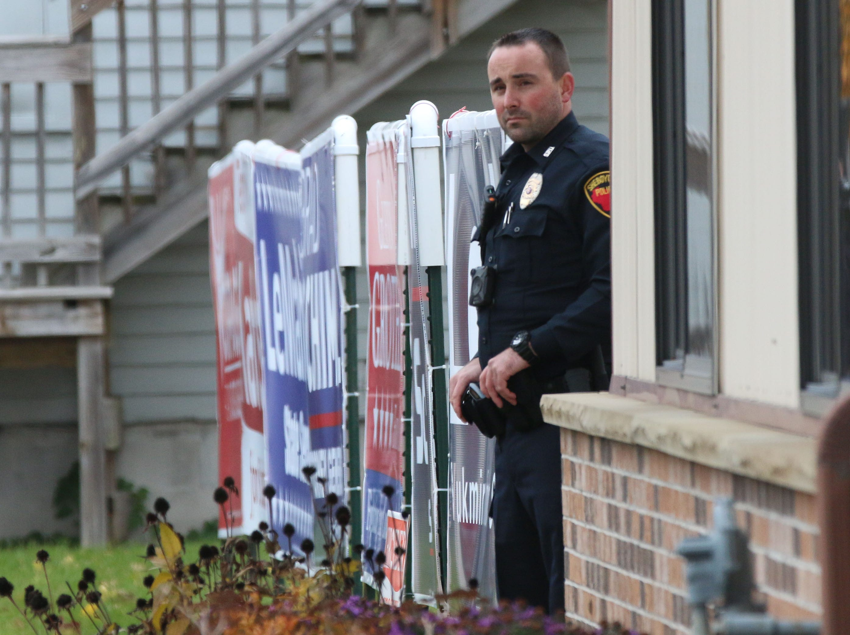 A Sheboygan police officer stands outside of the GOP headquarters while waiting for a Republican campaign rally to end, Tuesday, October 30, 2018, in Sheboygan, Wis. Eric Trump came to Sheboygan to help Wisconsin Republicans.