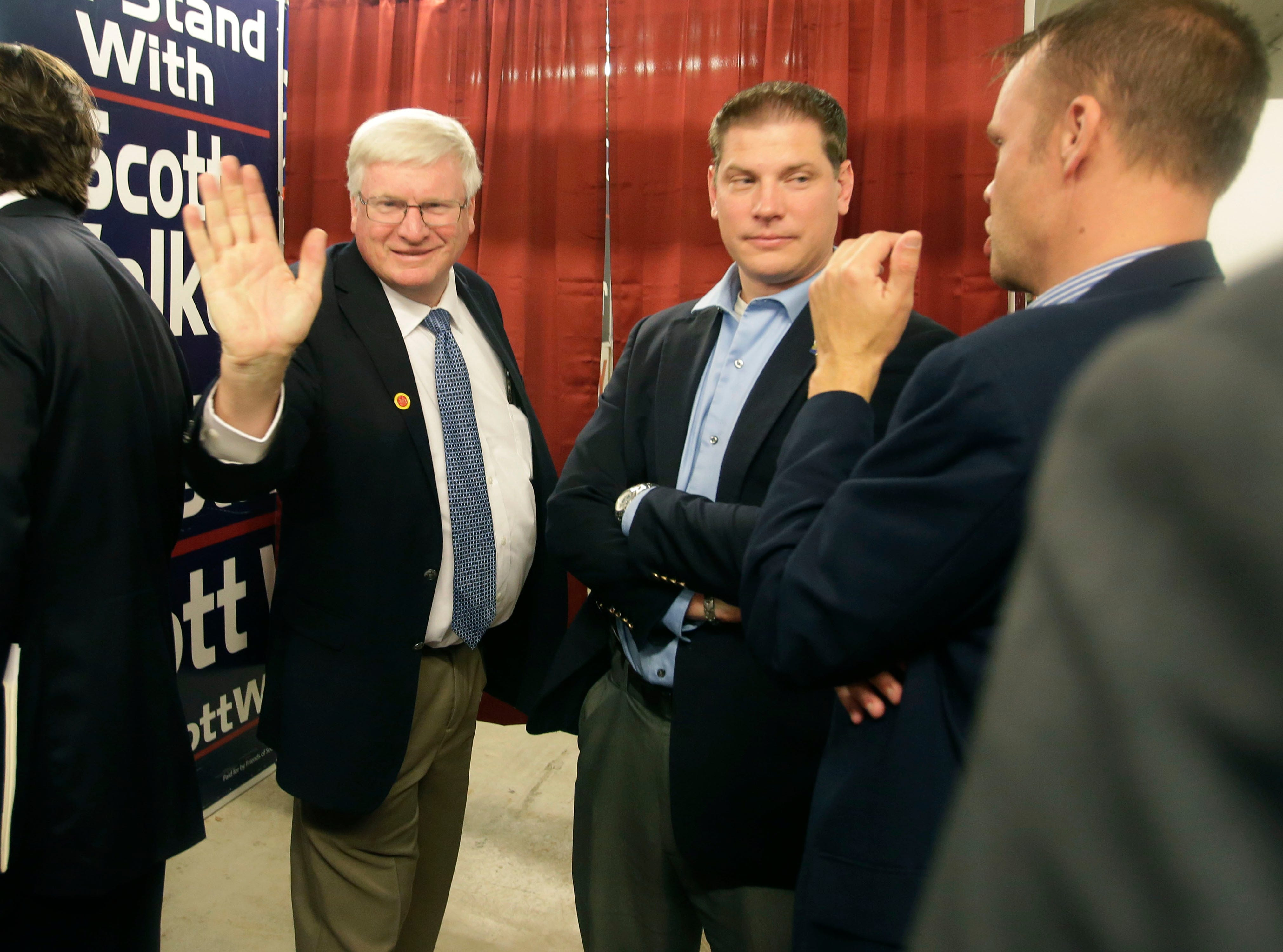 U.S. Representative Glenn Grothman, left, waves, while standing next to State Representative Tyler Vorpagel, middle and State Senator Devin LeMahieu, back to camera, Tuesday, October 30, 2018, in Sheboygan, Wi