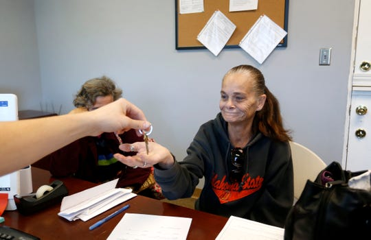 Julie Starbuck is handed the keys to her new apartment at the Franciscan Villa apartments on Wednesday, Oct. 24, 2018.