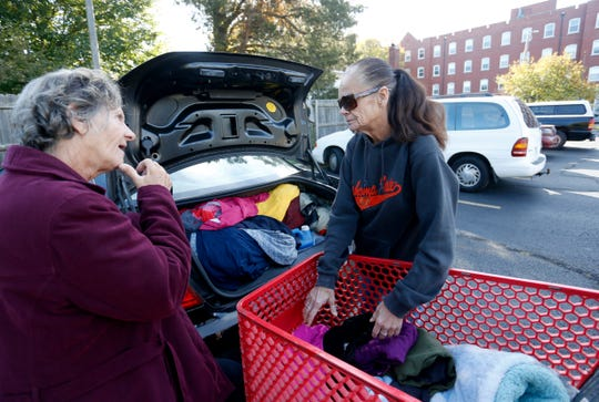 Julie Starbuck, with the help of her friend Debra Crouch, moves her belongings into her new apartment after being homeless for more than eight months.