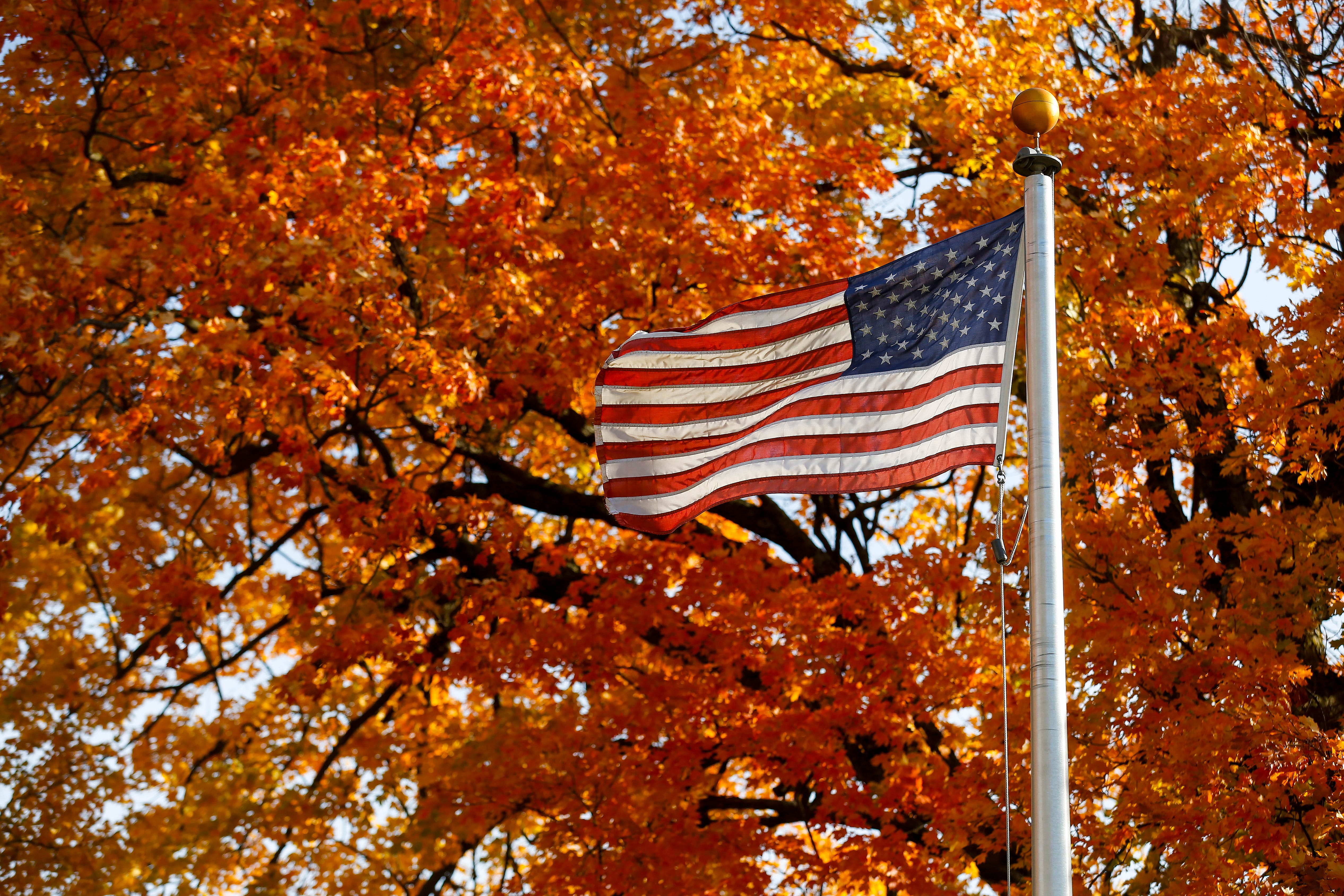 The American flag blows in the breeze in front of colorful fall leaves at Lincoln Memorial Cemetery on Tuesday, Oct. 30, 2018.