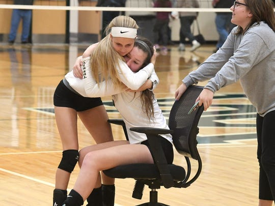 Wilson Memorial's Sarah Johnson hugs Cassidy Davis who sits in a rolling chair on the court with them after their loss to East Rockingham in the Shenandoah District championship match played in Fishersville on Monday, October 29, 2018. Davis went down with an injury during the match but returned in the chair to cheer for her teammates.