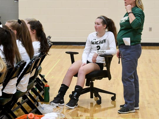 Wilson Memorial's Cassidy Davis returned to the gym in a rolling chair to sit behind her teammates to cheer them on during the  Shenandoah District championship match played in Fishersville on Monday, October 29, 2018.