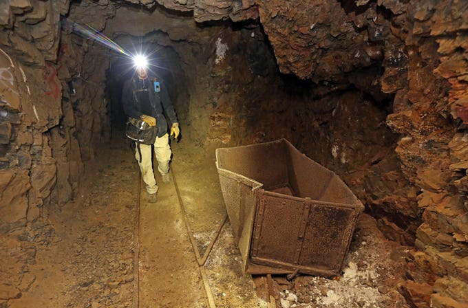 """Jeremy MacLee walks through a mine near Eureka, Utah, on Aug. 14, 2018. Underneath the mountains and deserts of the U.S. West lie hundreds of thousands of abandoned mines. Still, not everyone wants to see the mines closed. """"Nobody has walked the path you're walking for 100 years,"""" said MacLee, who uses old mining documents and high-tech safety equipment to find and explore forgotten holes, mostly in Utah. He also lends his expertise to searches for missing people."""