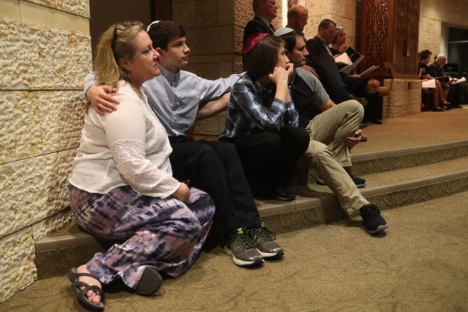The Fantle family sits together and comforts each other during a service honoring the lives of the victims of the shooting at Tree of Life Synagogue in Pittsburgh, Pa. held at Temple Israel in Tallahassee, Fla. Monday, Oct. 29, 2018.