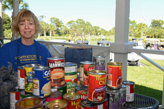 Volunteer Vicki Casabo collects cans of food in exchange for Mulligans at the Be a Hunger Hero golf tournament to benefit Sarah's Kitchen.