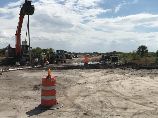 Workers construct an access road to the 40-acre site where City Electric Supply plans to build a new facility.