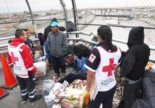 Mexican Red Cross workers check on migrants camped near the summit of the Paso Del Norte international bridge waiting to enter the U.S. on Tuesday. They said 38 migrants, including 15 Cubans, 11 Guatemalans, two Russians and a Honduran, were camped on the bridge.
