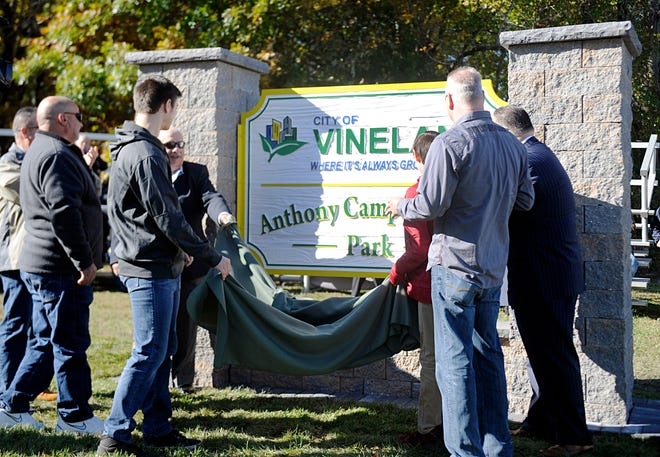 Relatives of former Vineland Mayor Anthony Campanella Sr. joined with city officials on Tuesday to unveil a new sign at what was South Vineland Park on West Elmer Road. The park was renamed after Campanella, who died in November 2015. City Council President Paul Spinelli (left) and Mayor Anthony Fanucci (right) hold ends of the sign cover.