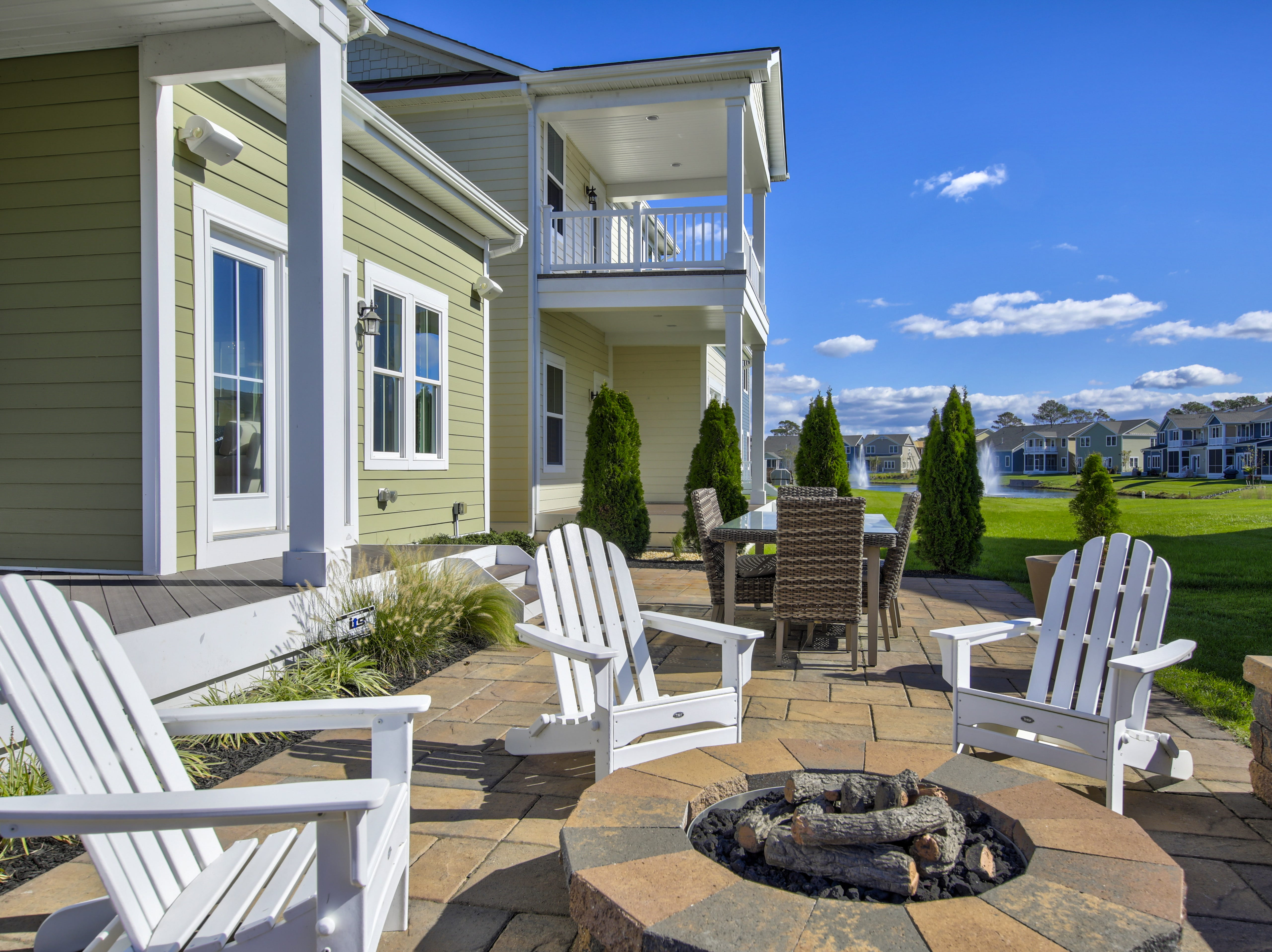 The outdoor space in back of the model home at The Overlook in Selbyville offers  a fire pit , installed on a paver patio.