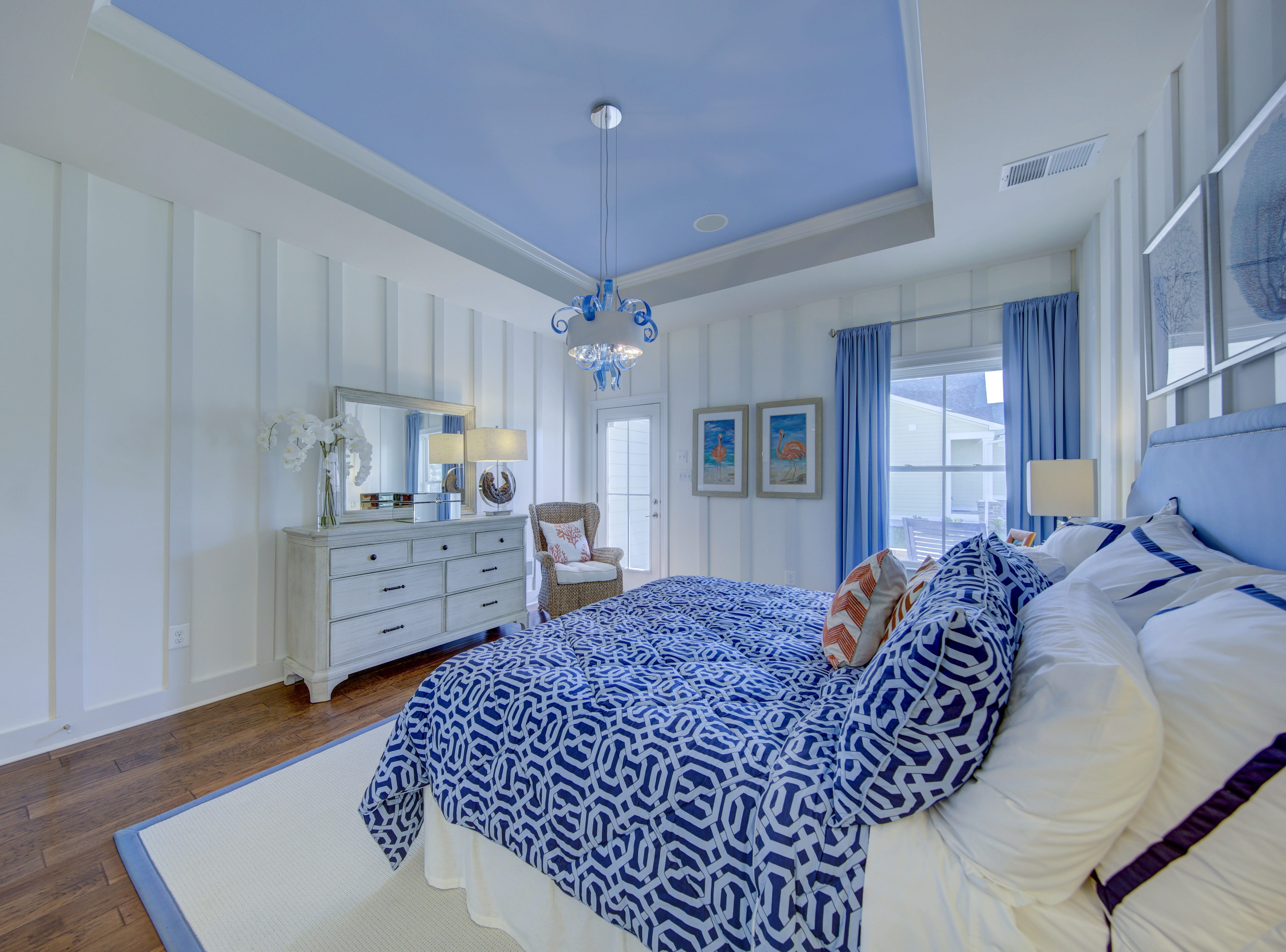 The first-floor master bedroom of the model home in The Overlook at Selbyville has a tray ceiling and custom moldings on the walls.