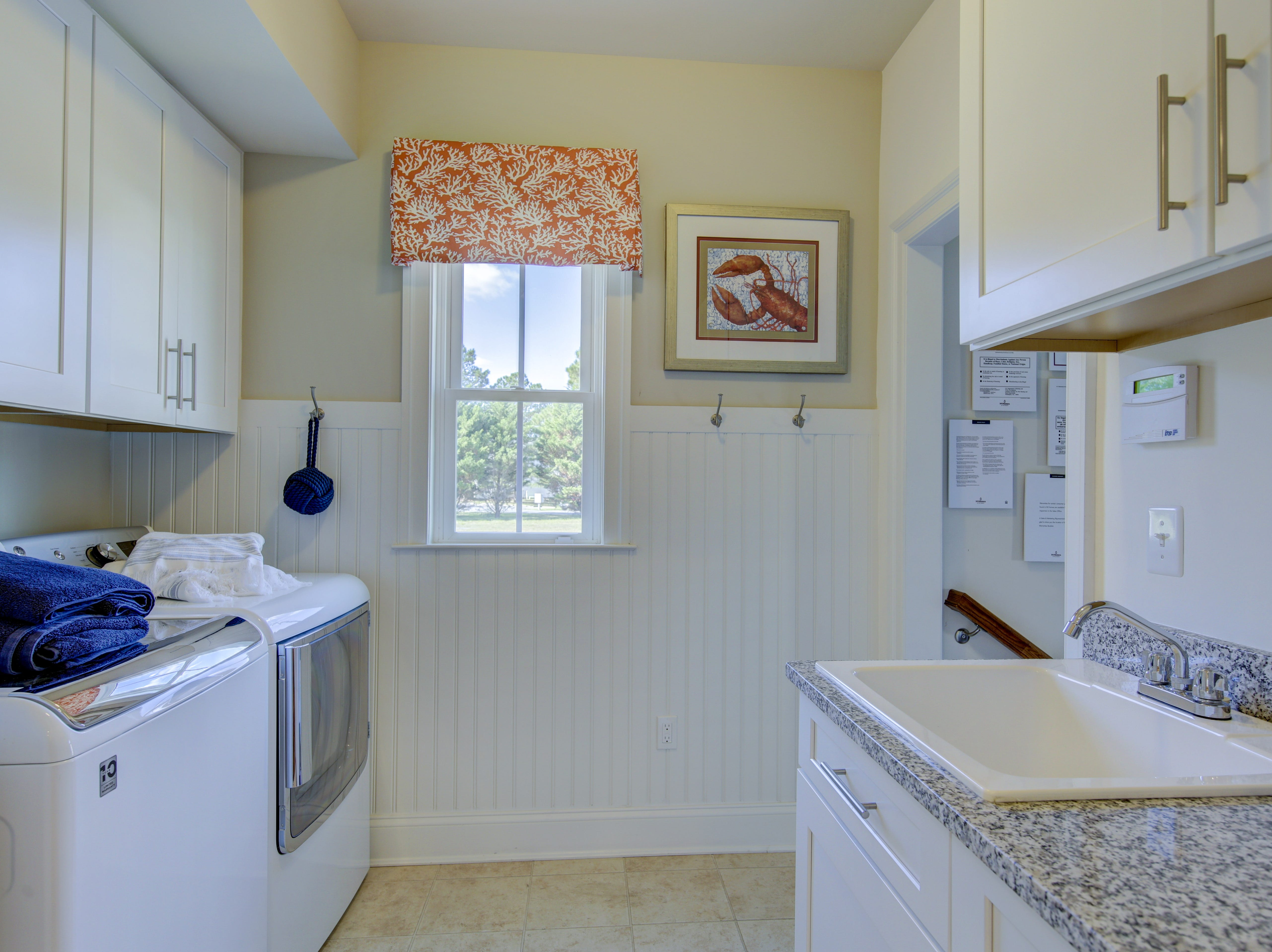 A combination mudroom and laundry room has custom wainscoting in The Overlook's model home in Selbyville.