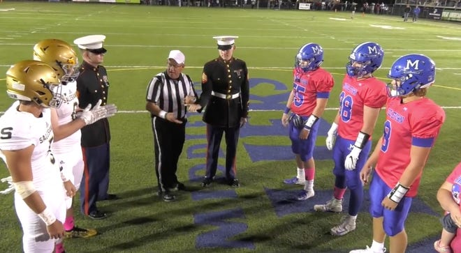 Referee Dennis Craighton does the coin toss for a Salesianum-Middletown game.
