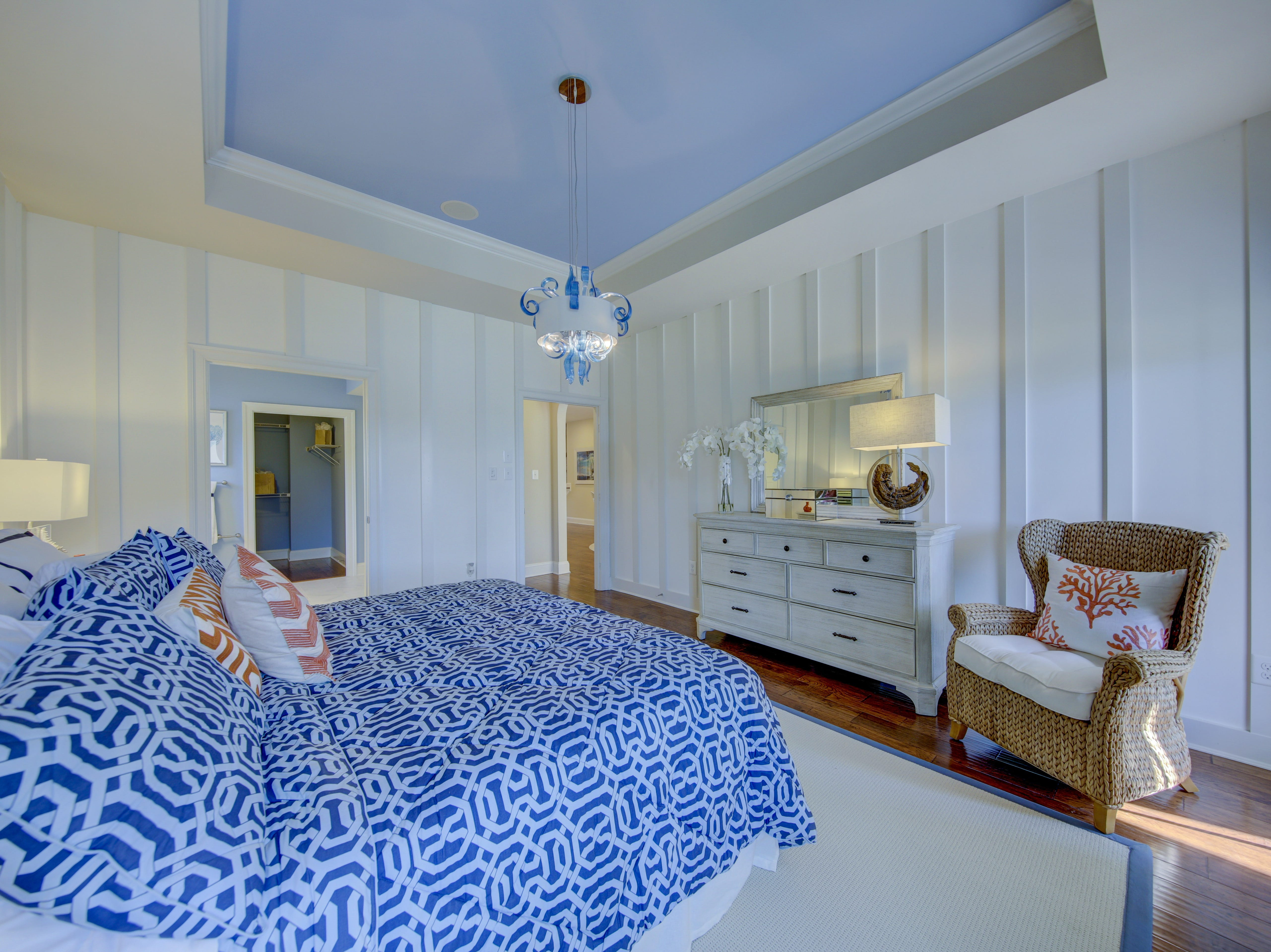 The first-floor master bedroom has a tray ceiling and custom moldings on the walls.