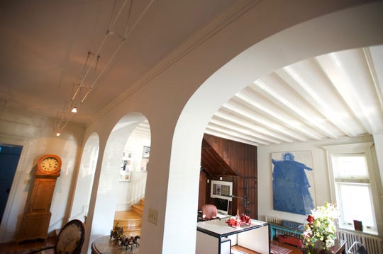 The first floor of Postles House is being used as an office for the owner's design firm, and shows off the architectural elements like its arched doorways and beamed ceiling.