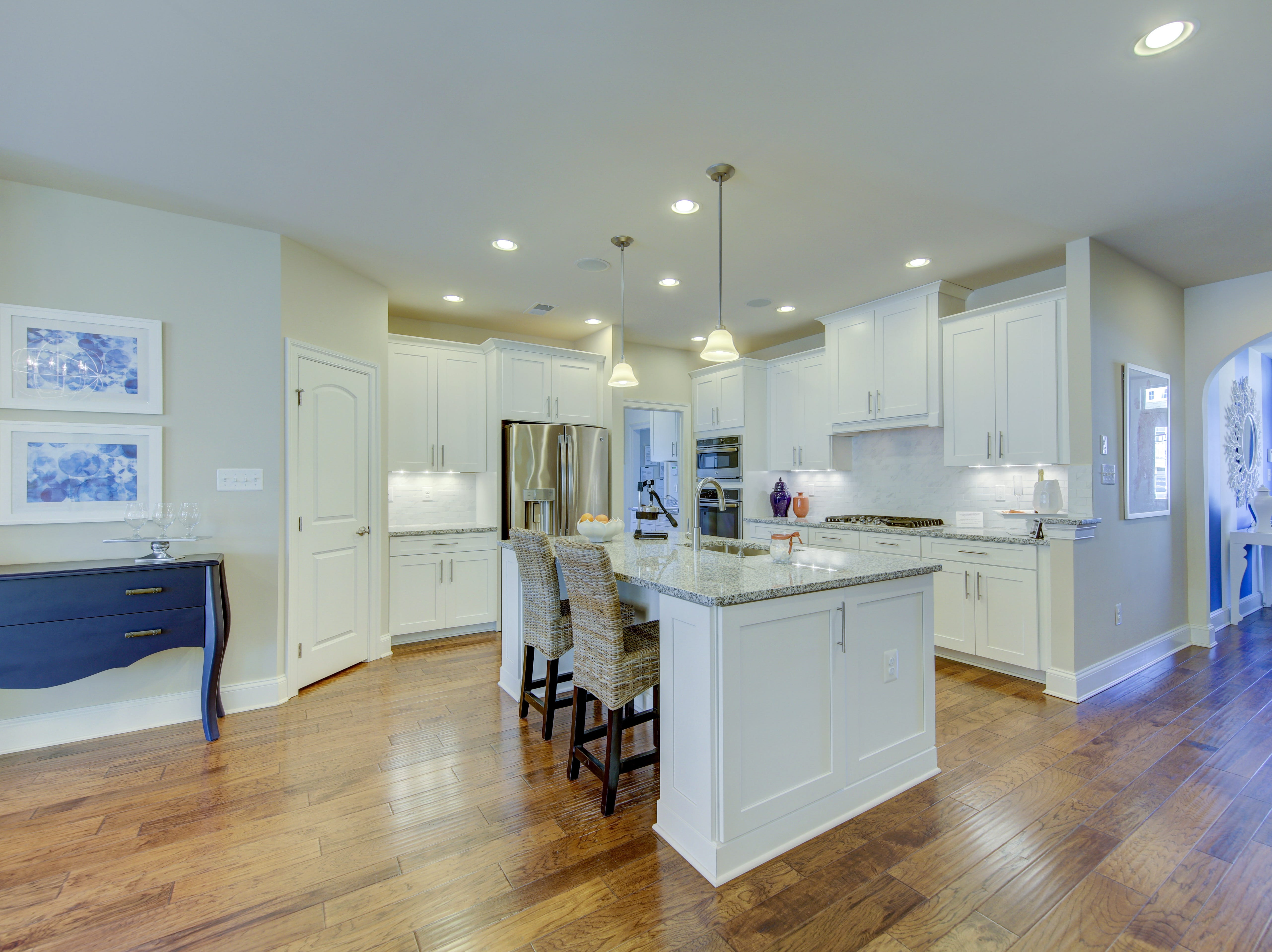 The open kitchen offers granite countertops, an upgrade, and stalnless steels appliances in the model home in The Overlook at Selbyville.