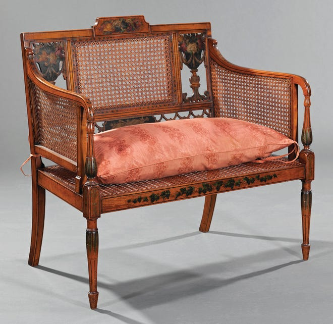 "Caned arms, back and seat make this settee a little different. It was made in the 19th century in the ""Adam taste."" Neal Auction Co. in New Orleans sold it for $1,250."