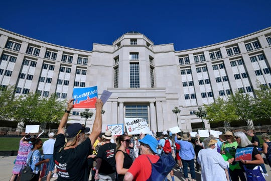 Demonstrators rally outside the Michigan Hall of Justice in Lansing, July 18 as the Michigan Supreme Court heard arguments about whether voters should be able to pass a constitutional amendment to change how the state's voting maps are drawn.