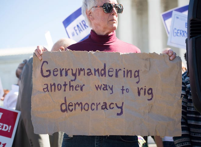 A protester marches outside the Supreme Court on Oct. 3, 2017 as the court heard arguments in a Wisconsin gerrymandering case. The court eventually ruled that Wisconsin Democrats didn;t have standing to sure.