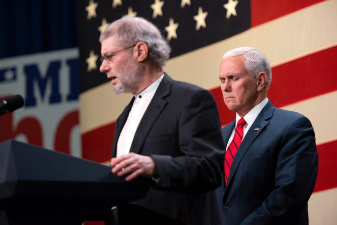 Vice President Mike Pence, right, prays with Rabbi Loren Jacobs of Bloomfield Hills' Congregation Shema Yisrael for the victims and families of those killed in the Pittsburgh synagogue shooting at a rally for Republicans in Oakland County on 29, 2018.