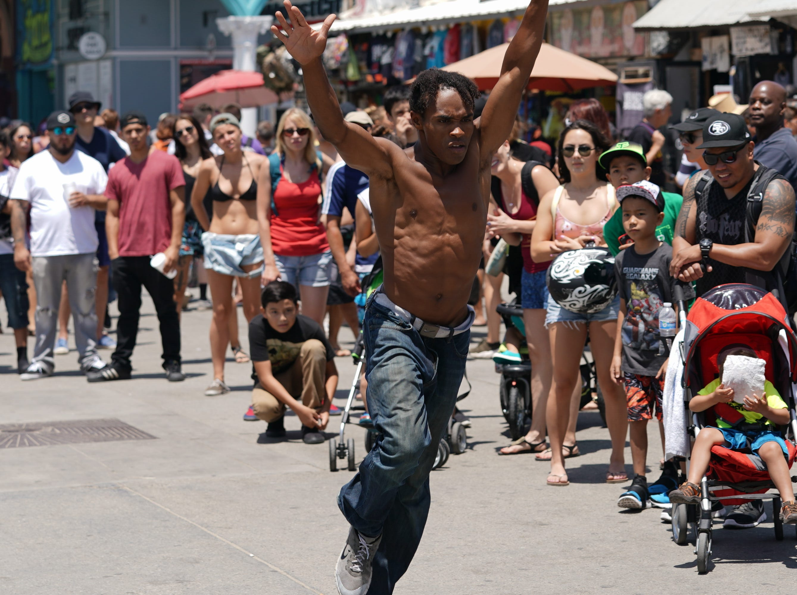 A street performed prepares to do a flip in Venice Beach.
