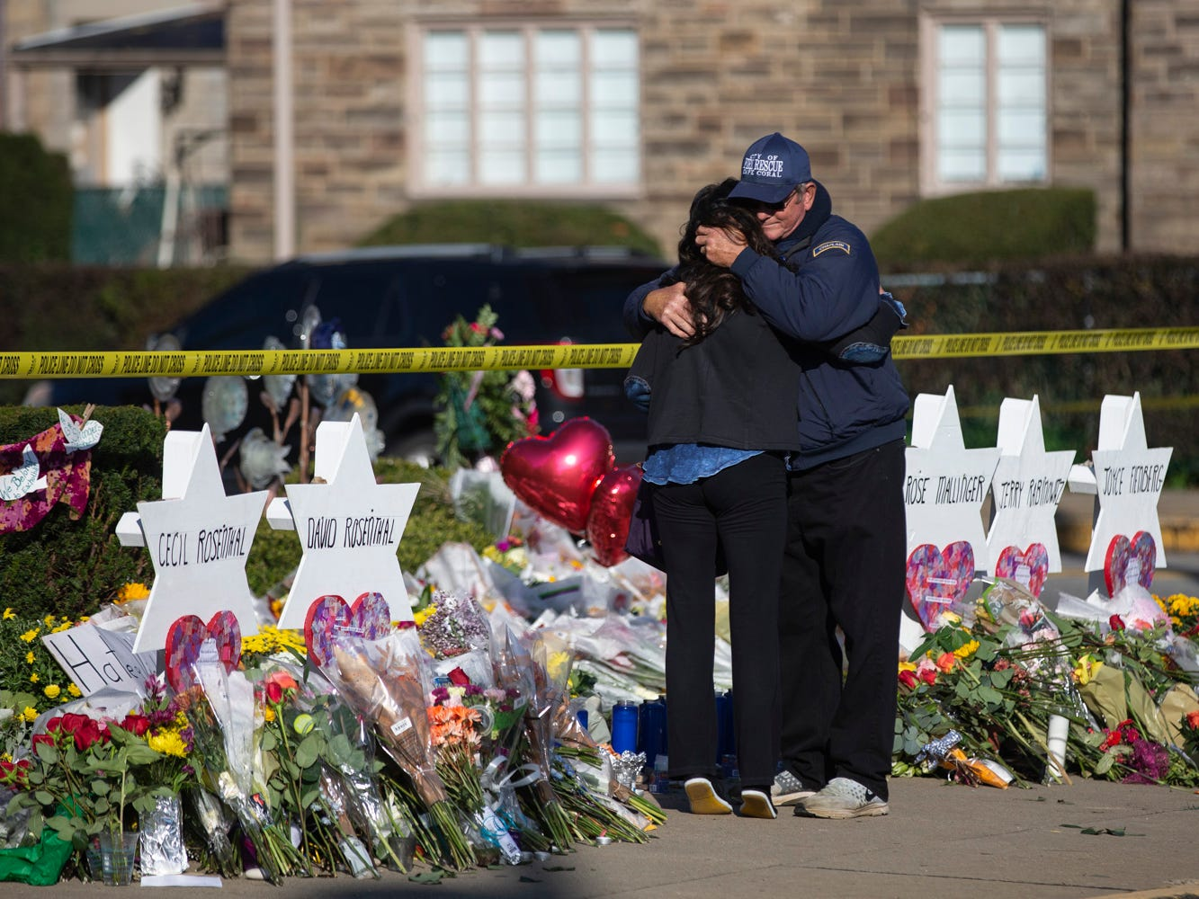 "Florida native and chaplain Bob Ossler, right, hugs Julianne Statnick as she visits a tribute to shooting victims along Shady Avenue in Pittsburgh, Pennsylvania on Tuesday morning. ""I grew up here,"" Statnick said. ""I was in Ireland when this happened so now I'm just here spreading love."" Oct. 30, 2018 (Via OlyDrop)"
