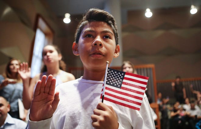 Davies Garcia holds a flag during a naturalization ceremony on Sept. 14, 2018, in Los Angeles.