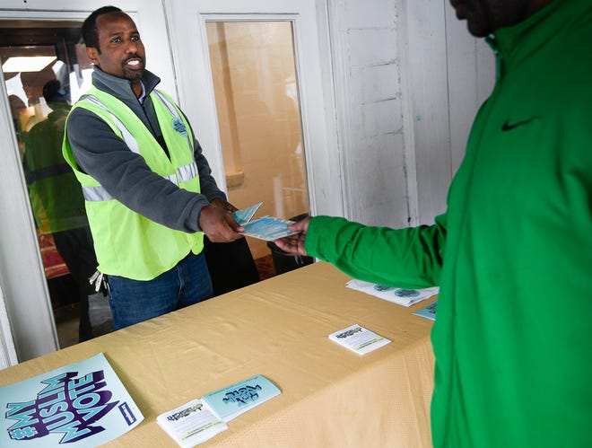 Abdirizak Bahale of the American Muslim Advisory Council hands out information about early voting at the Al-Farooq muslim center after a prayer service Friday, Oct. 26, 2018, in Nashville, Tenn.