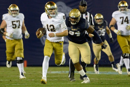 Notre Dame quarterback Ian Book runs the ball against Navy during their game in 2018.