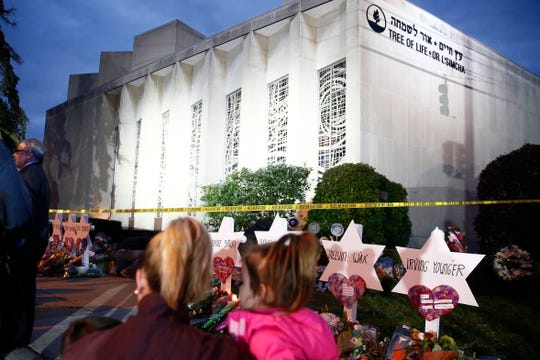 A family looks on at the Star of David memorials at the Tree of Life Synagogue days after a mass shooting in Pittsburgh, Pennsylvania.