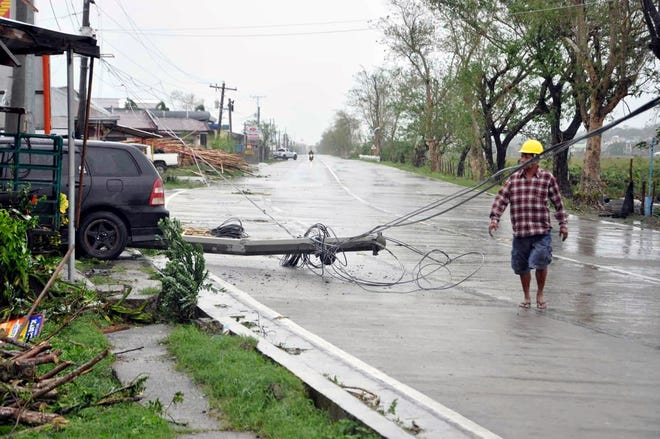 A resident walks next to a toppled electric pole after Typhoon Yutu slammed the northeastern Philippines on Tuesday, Oct. 30, 2018.
