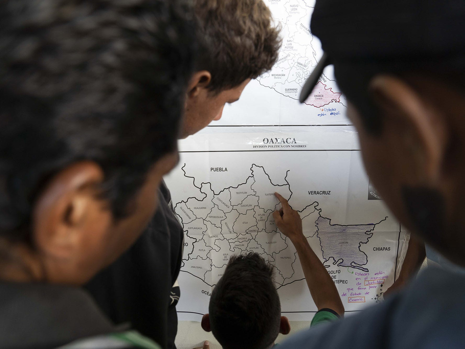 Central American migrants traveling in a caravan looks at Oaxaca map while they move north towards United States.