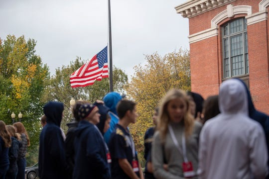 The American flag flies at half-staff as a group of students waits to enter the U.S. Holocaust Memorial Museum in Washington.