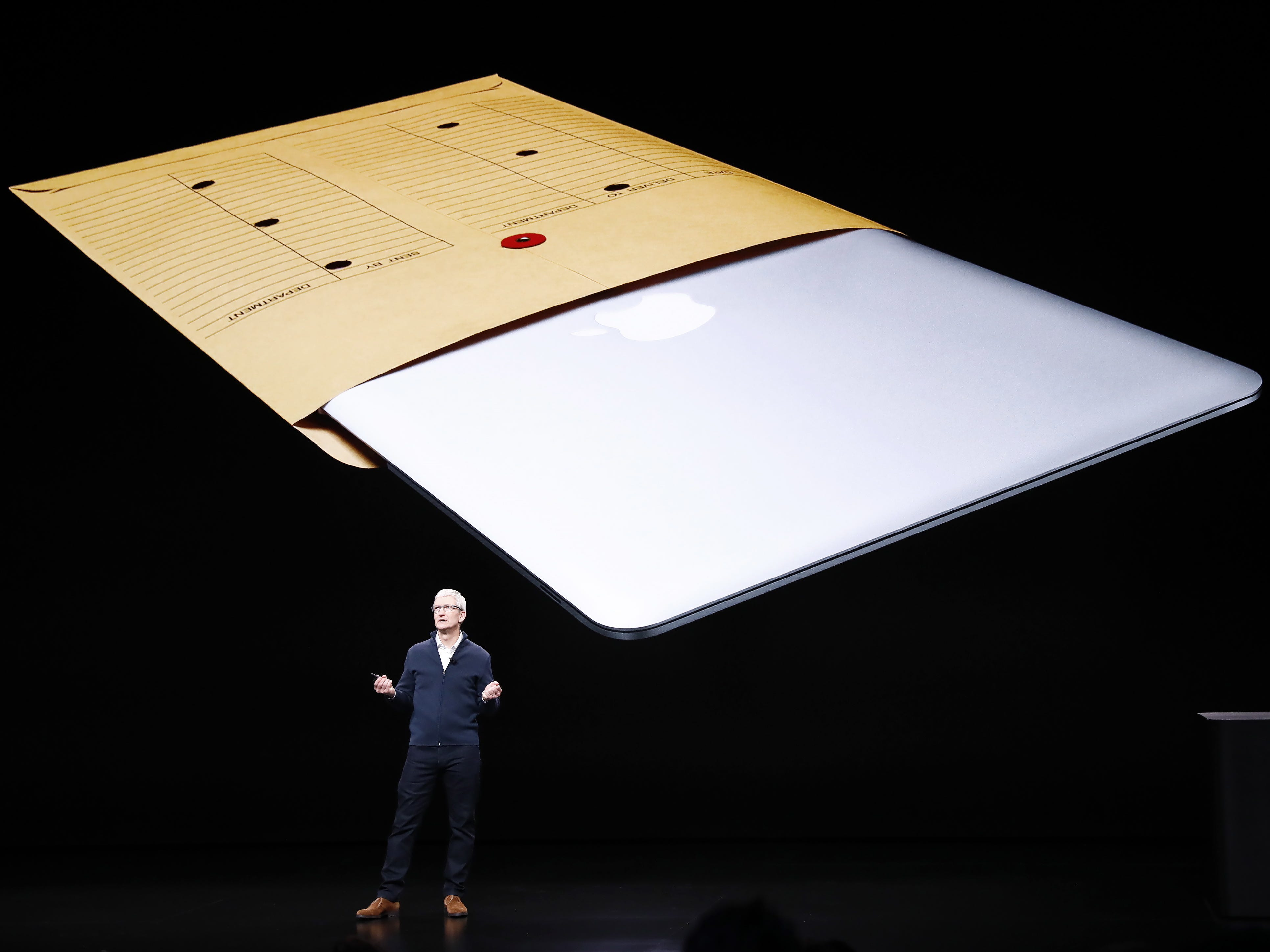 Apple CEO Tim Cook speaks with a Macbook Air on a screen behind him during an Apple special event at the Howard Gilman Opera House at the Brooklyn Academy of Music before the start of an Apple event in New York, Tuesday, Oct. 30, 2018.