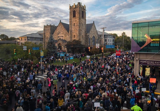 """Thousands march past the Sixth Presbyterian Church at the intersection of Forbes and Murray in Pittsburgh during the """"Stand together in solidarity with the Pittsburgh Jewish Community,"""" event. Protesters against hate crimes and gun violence came together and marched through the streets singing Jewish songs and prayers."""