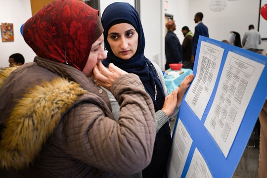 """Salwa Barwari and Kasar Abdulla look at a sample ballot during a """"Vote Together Party"""" hosted by the American Muslim Advisory Council before voting at Casa Azafran Friday, Oct. 26, 2018, in Nashville, Tenn."""