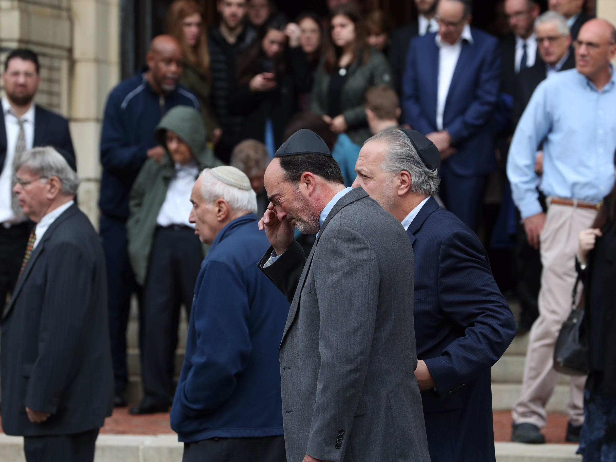 Mourners stand outside as the caskets of brothers David and Cecil Rosenthal are carried out together at the conclusion of funeral services at the Rodef Shalom Congregation in Pittsburgh, Pa., Tuesday, Oct. 30, 2018.