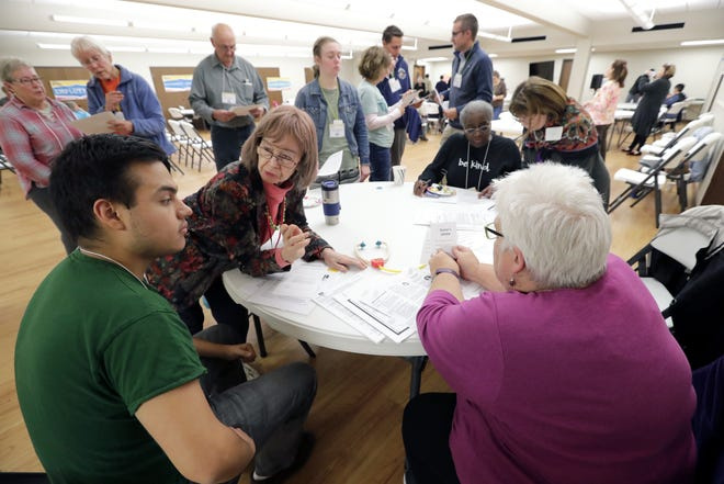 "Lawrence University student Daniel Vaca, left, of Quito, Ecuador, uses an ""interpreter"" to communicate with a ""doctor"" as he participates in the Walk In Our Shoes simulation event Tuesday at Memorial Presbyterian Church in Appleton."