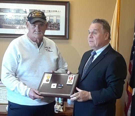 Rep. Chris Smith (right) presents replacement medals to Bernard Ebner.