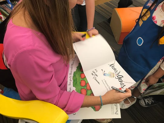 Shannon Pulaski signs copy of her children's book Mom's Genes earlier this month for the girl scouts at the Millstone Township Primary School.