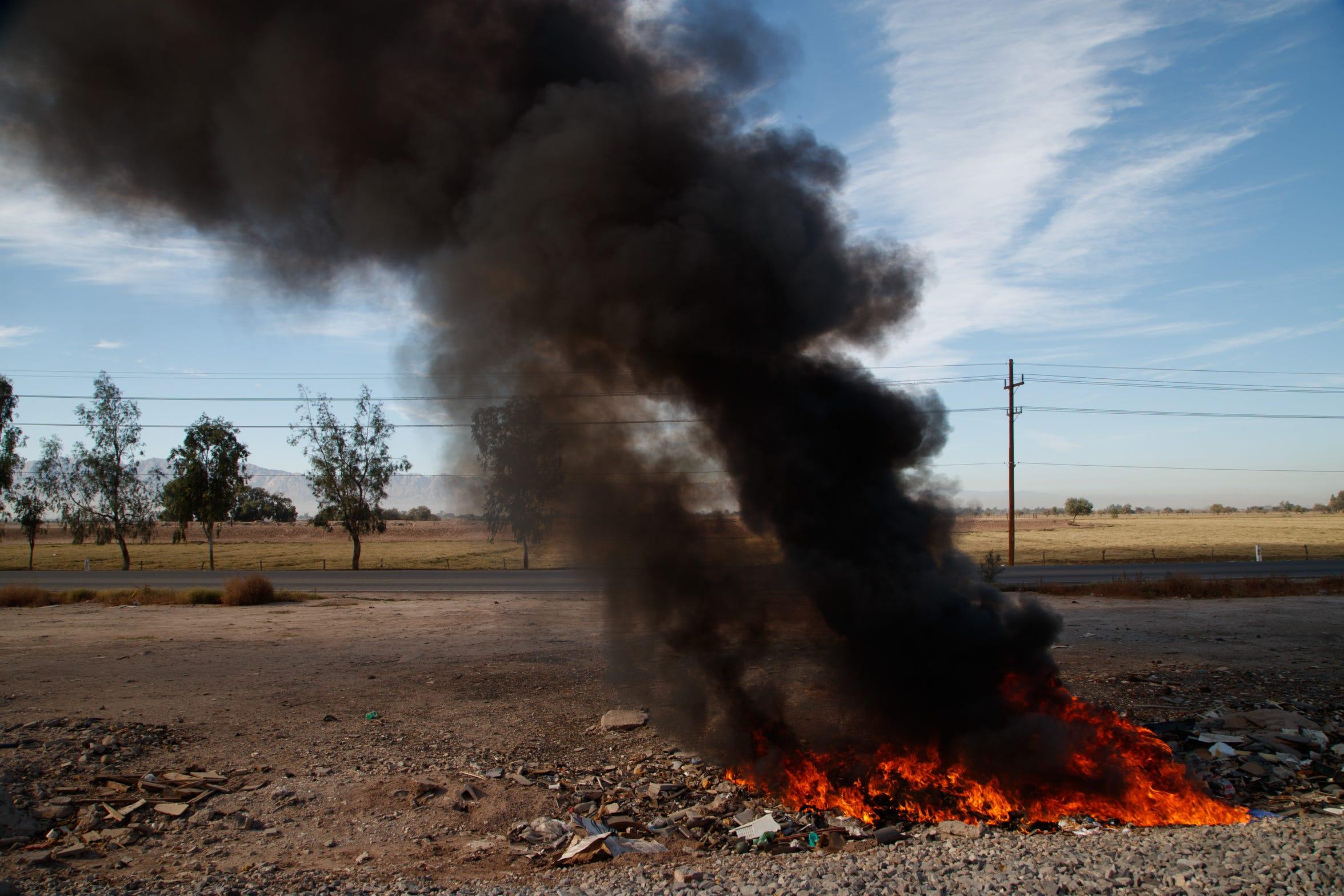 Humo negro brota de un apiladero de basura que es incendiado en un campo, cerca de Mexicali.