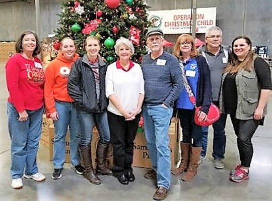Volunteers gather around a Christmas tree getting ready to pack boxes as part of Operation Christmas tree.