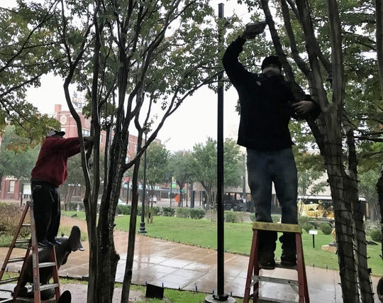 Noel Robles, left, and Andrew Flores of Christmas Decor work in the rain on Halloween to put up Christmas lights in Everman Park.