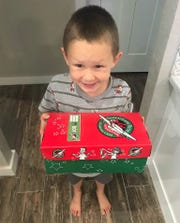 Rylan Loudermilk holds a box for Operation Christmas Child