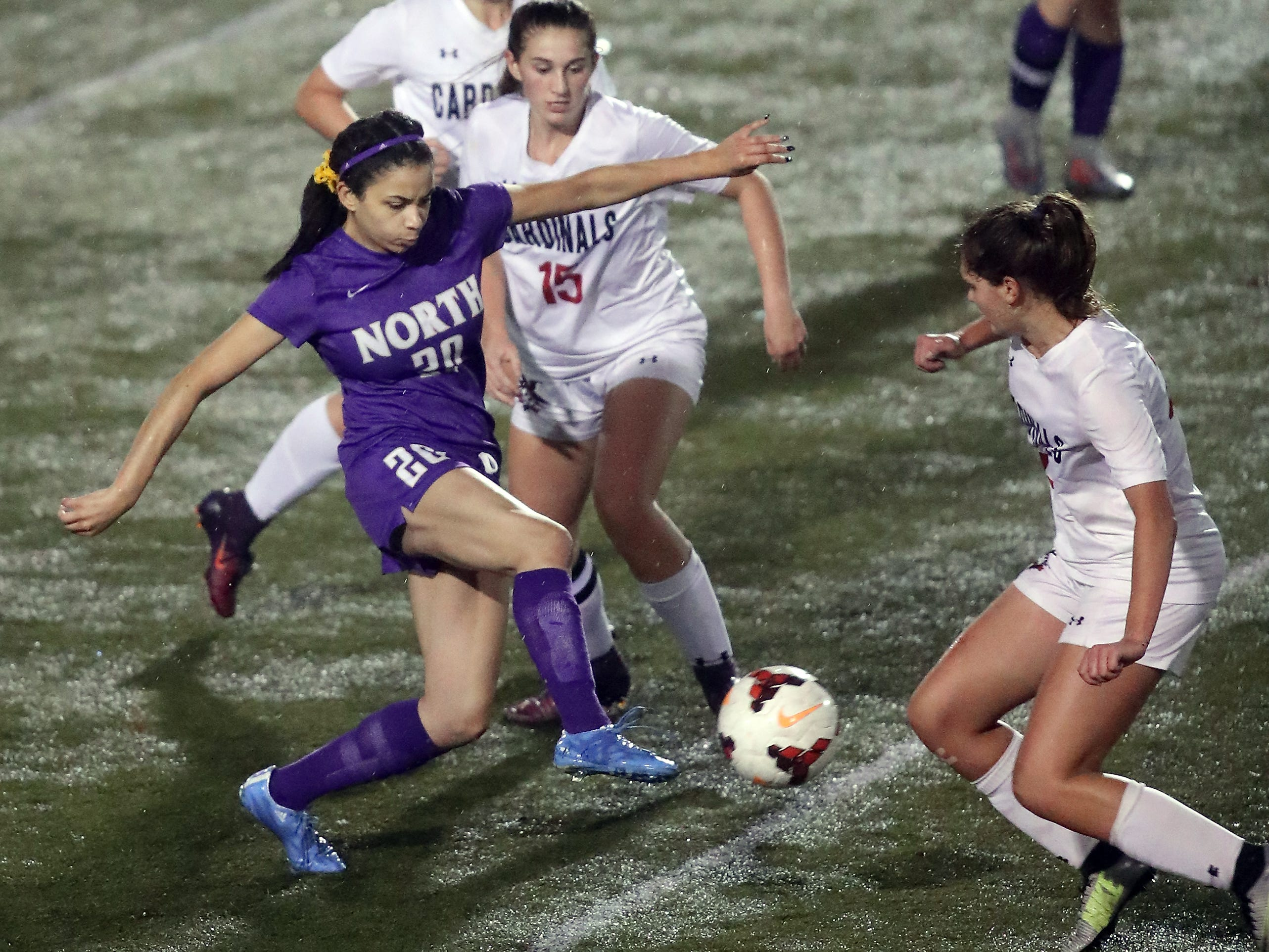 North Kitsap's Isla Lester (left) moves the ball through Orting defenders Katie Harvie (center) and Hailey Hansen (right) in Poulsbo on Tuesday, October 30, 2018.