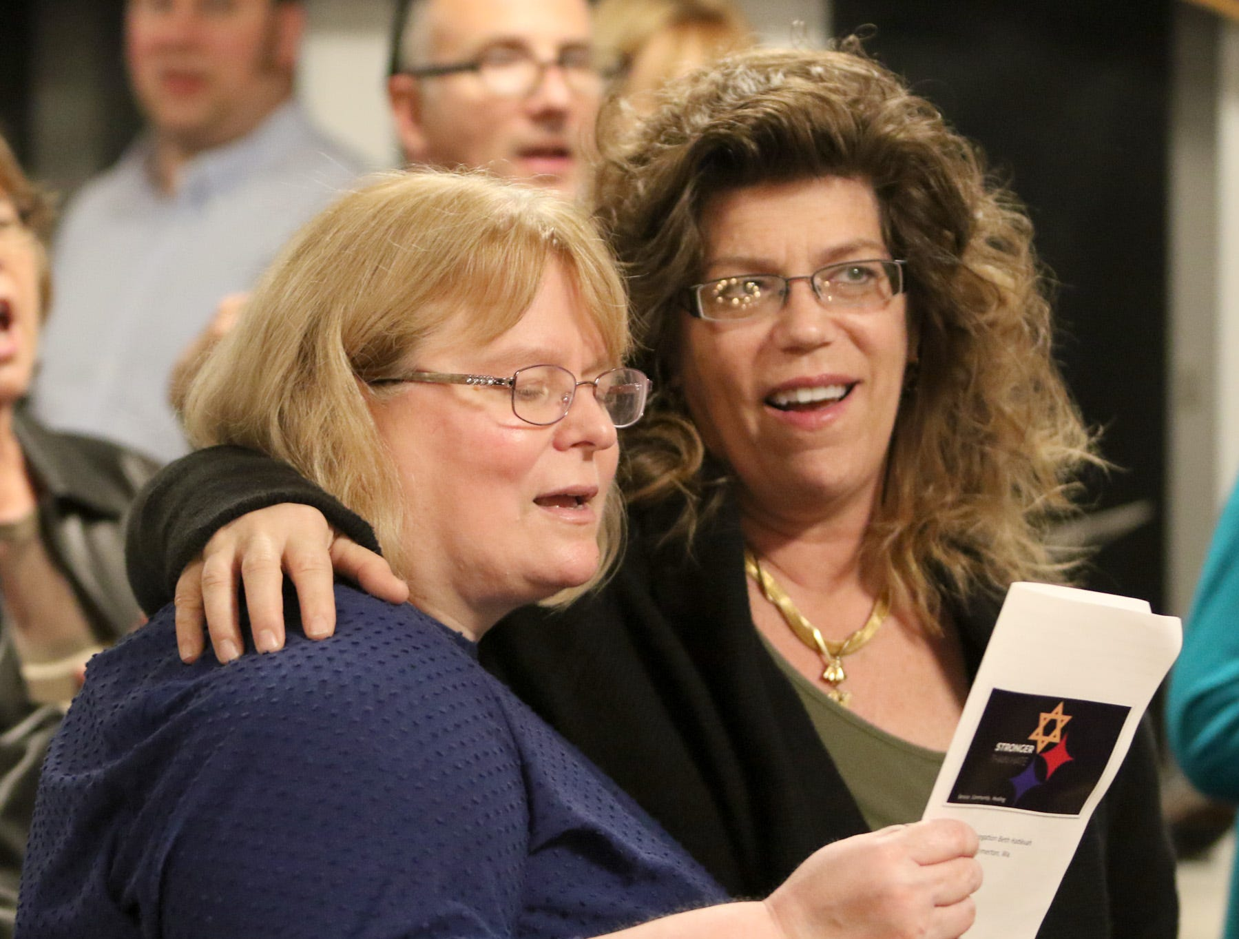 """The Beth Hatikvah (House of Hope) Synagogue in Bremerton held a memorial service for the Tree of Life Synagogue shootings Tuesday night in Bremerton. Patty Seljestad, left, and Andrea Dolan-Potter join in singing """"This Little Light of Mine"""" during the service."""